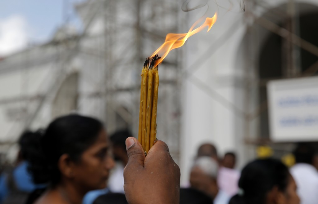 A Sri Lankan Roman Catholic devotee holds candles up as he prays out Side the St. Anthony's church, one of the sites of Easter Sunday attacks in Colom...