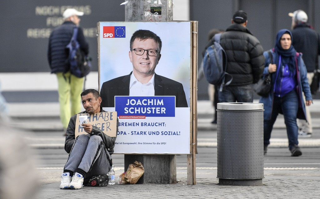 In this Tuesday, May 14, 2019 photo, a man with a sign reading 'I am hungry' begs in front of a poster showing SPD candidate Joachim Schuster for the