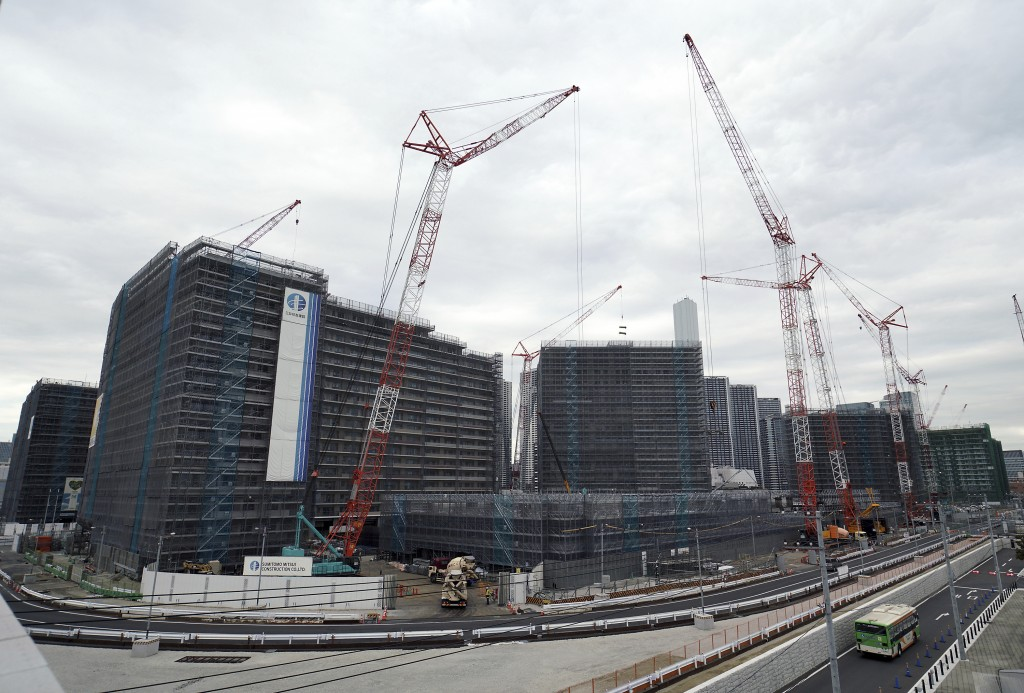 In this Feb. 12, 2019, photo, cranes continue to work at the construction site of the Olympic Village for the 2020 Tokyo Olympics in Tokyo. An IOC ins...