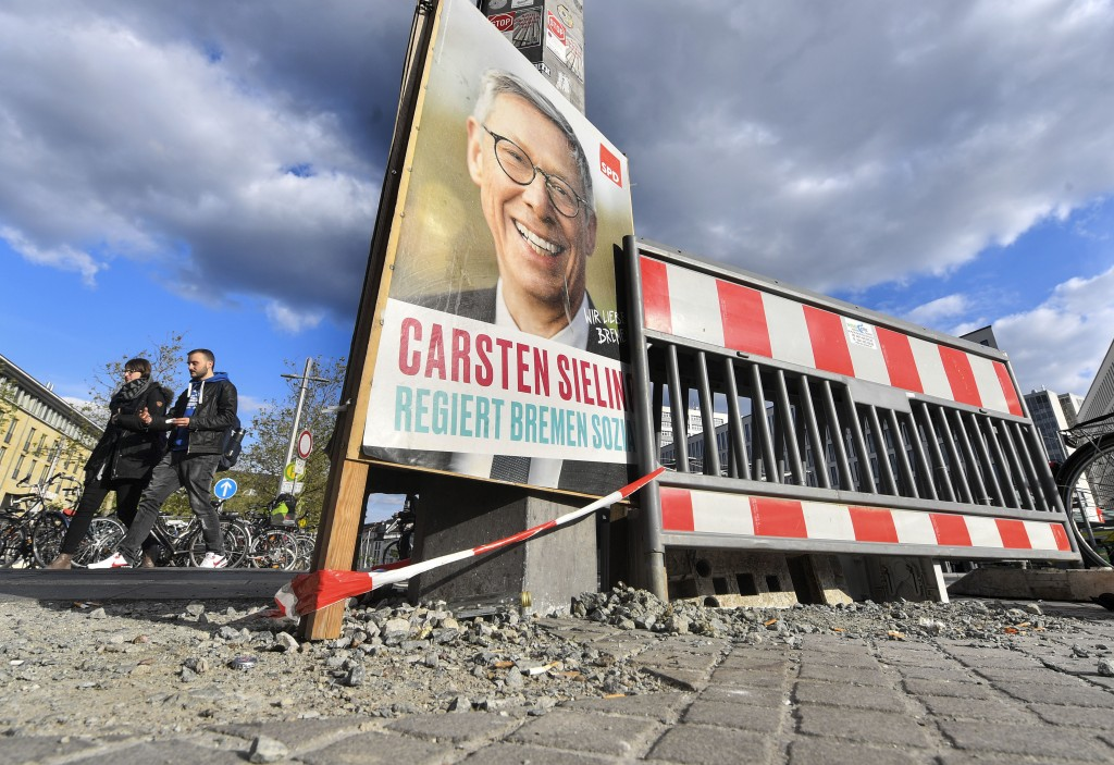 In this Tuesday, May 14, 2019 photo, a poster of SPD promotes the governing mayor of Bremen Carsten Sieling for the regional elections beside road wor
