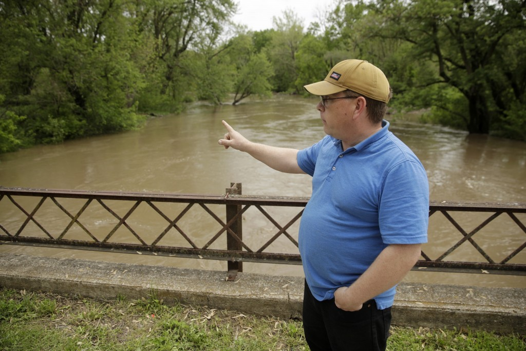 In this photo taken May 8, 2019, Jason Stooksbury checks out high water in the Fishing River from a condemned bridge in the small community of Mosby, ...