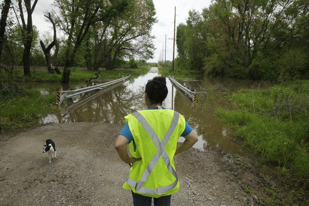 In this photo taken May 8, 2019, Tammy Kilgore as part of her duties with the local volunteer fire department, checks high water covering a road leadi...