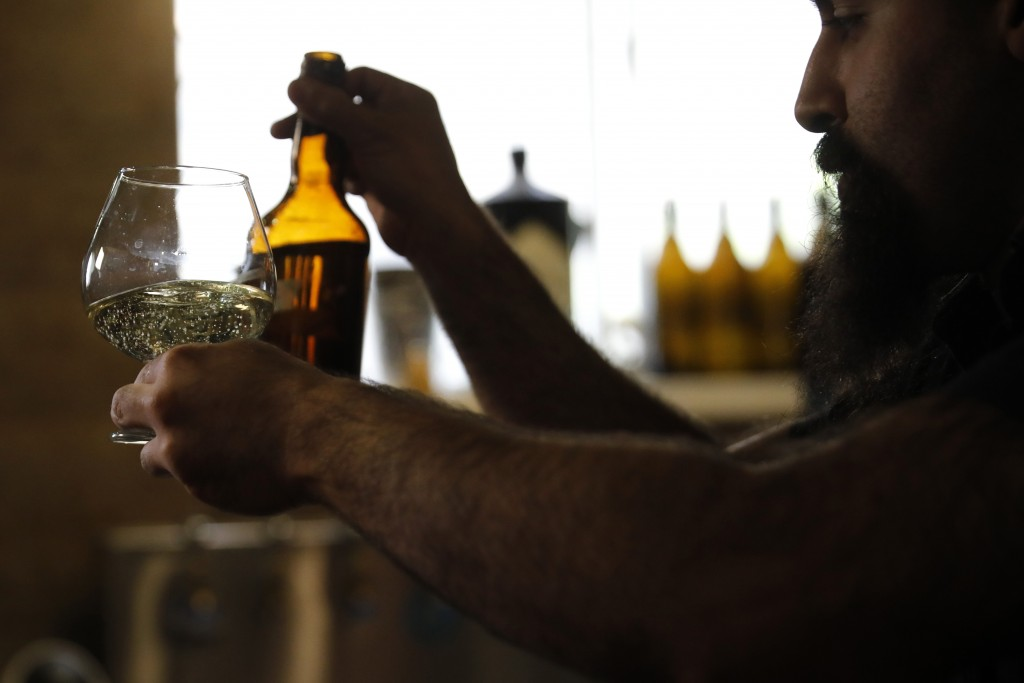 Craft brewer from Biratenu, the Jerusalem Beer Center, Shmuel Naky, right, pours beer during a press conference in Jerusalem, Wednesday, May 22, 2019.