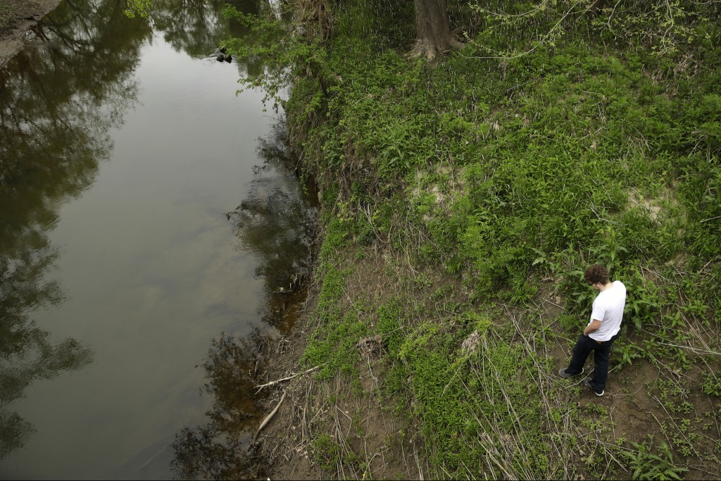 In this photo taken April 24, 2019, Gavin Podhorn looks for crawdads in the Fishing River, which periodically floods the small community of Mosby, Mo....