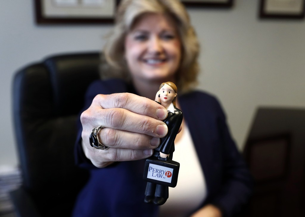 In this Tuesday, May 14, 2019, photo, business owner Meloney Perry, of Perry Law, shows off her miniature Meloney Perry Stress Doll as she poses for a...