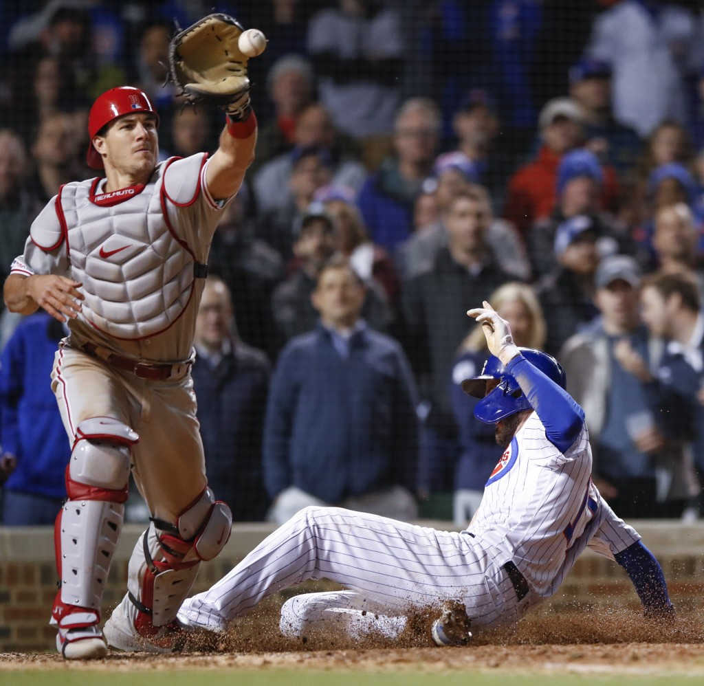Chicago Cubs' Kris Bryant, right, scores as Philadelphia Phillies' J.T. Realmuto, left, waits for the ball during the ninth inning of a baseball game,