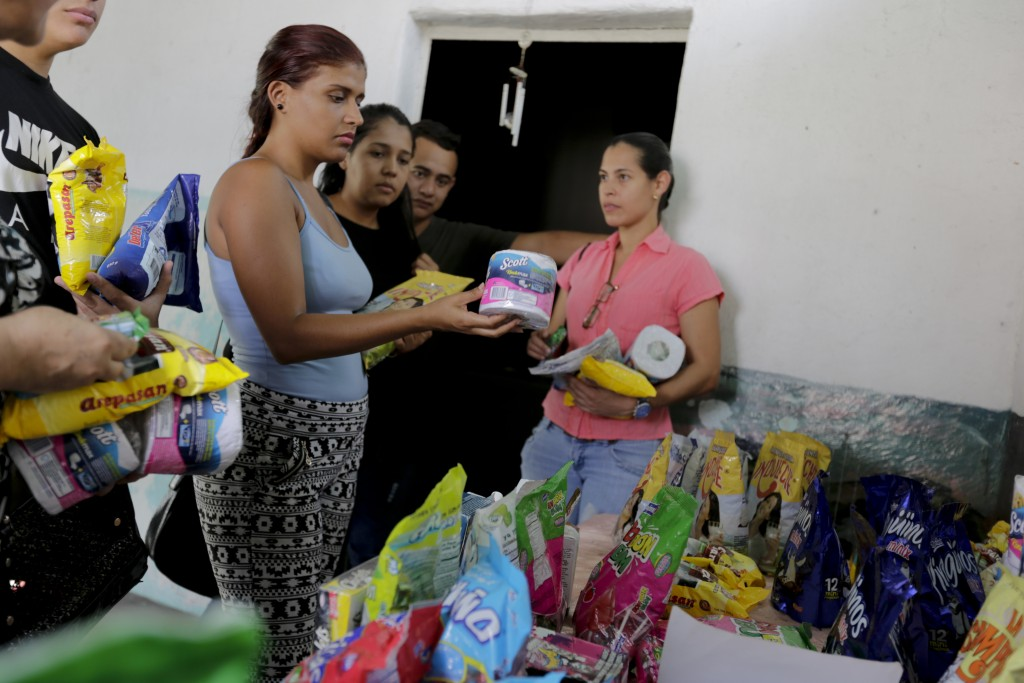In this April 11, 2019 photo, customers choose groceries that will be paid using cryptocurrency in Barquisimeto, Venezuela, Thursday, April 11, 2019. ...
