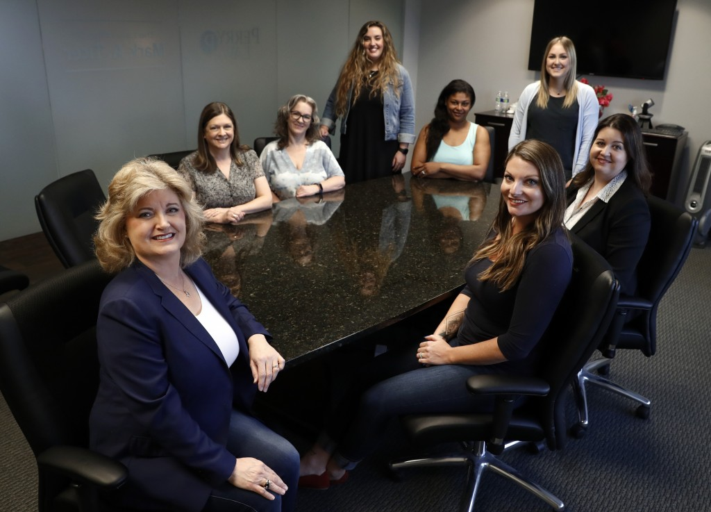 In this Tuesday, May 14, 2019, photo, business owner Meloney Perry, left front, poses for a photo with members of her staff, Karla Roush, from left re...