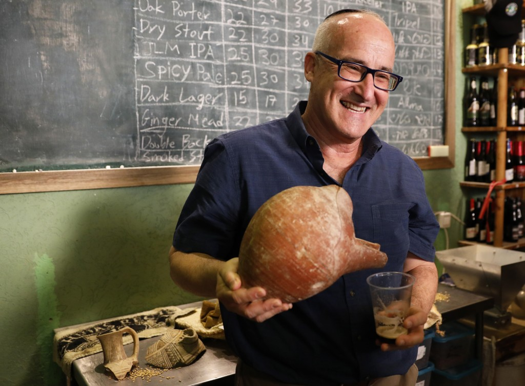Prof. Aren Maeir, from Bar Ilan University, holds an ancient jar and a glass of beer during a press conference in Jerusalem, Wednesday, May 22, 2019. ...