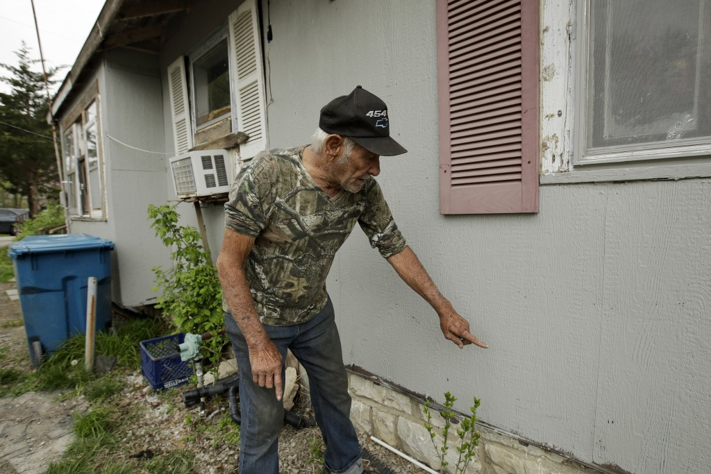 In this photo taken April 24, 2019, Elmer Sullivan shows the height of floodwater on one of the many times his house has flooded in the small communit...