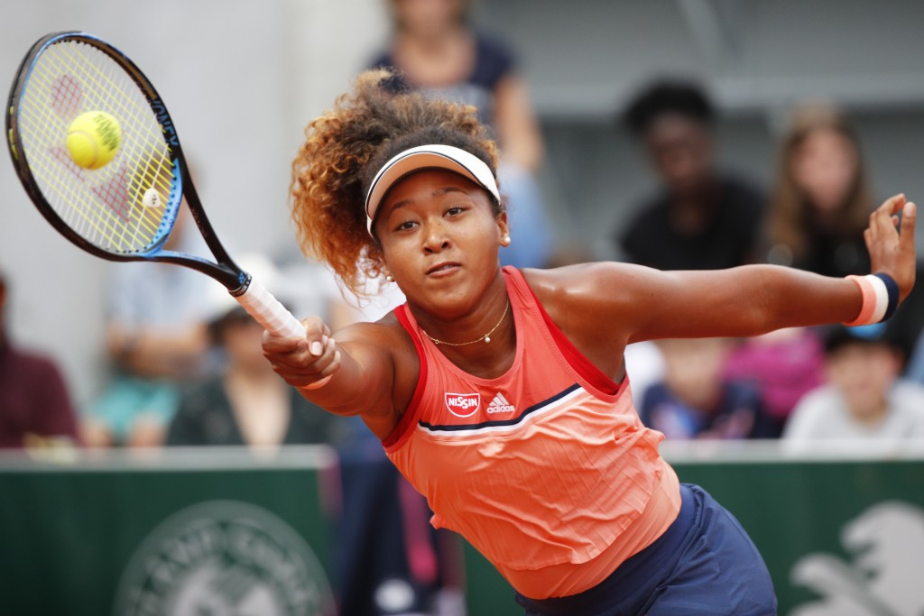 FILE - In this May 30, 2018, file photo, Japan's Naomi Osaka returns a shot against Kazakhstan's Zarina Diyas during their second round match of the F...