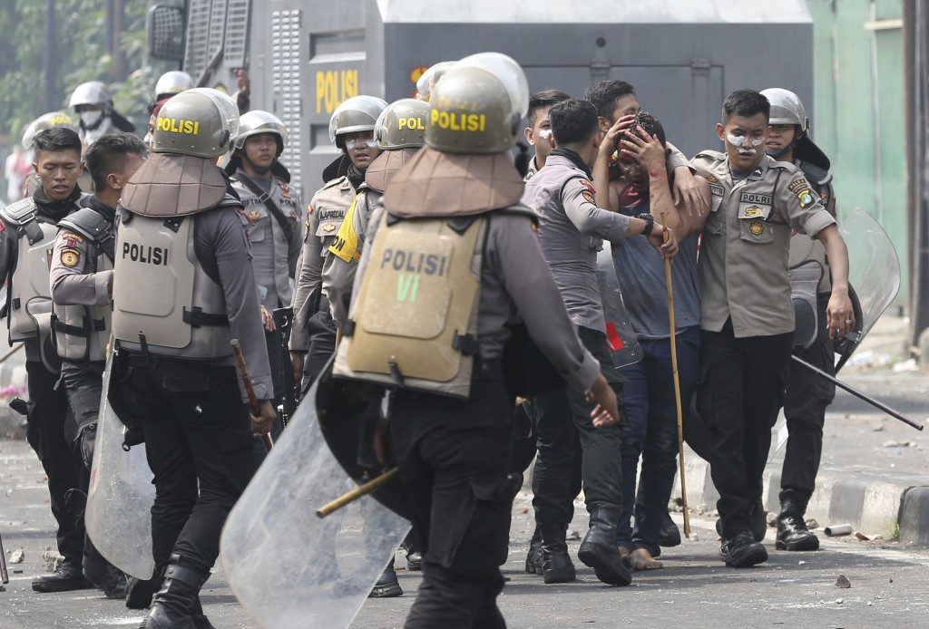 In this Wednesday, May 22, 2019, file photo, Indonesian police arrest a supporter of the losing presidential candidate in Jakarta, Indonesia. Supporte...