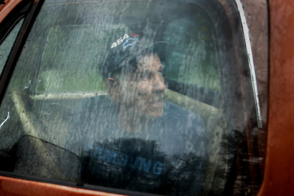 In this photo taken May 21, 2019, Elmer Sullivan shelters from the rain in his pickup truck as he watches rising waters in Fishing River in the small ...