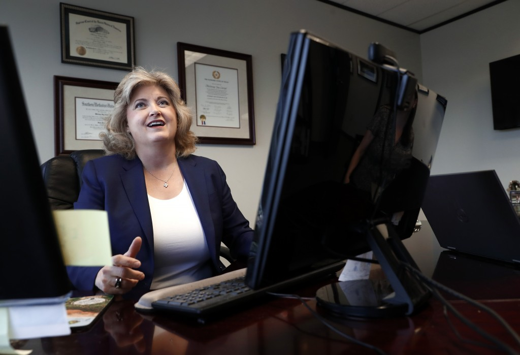 In this Tuesday, May 14, 2019, photo, business owner Meloney Perry sits behind her desk as she speaks with a staff member at her law firm in Dallas. P...