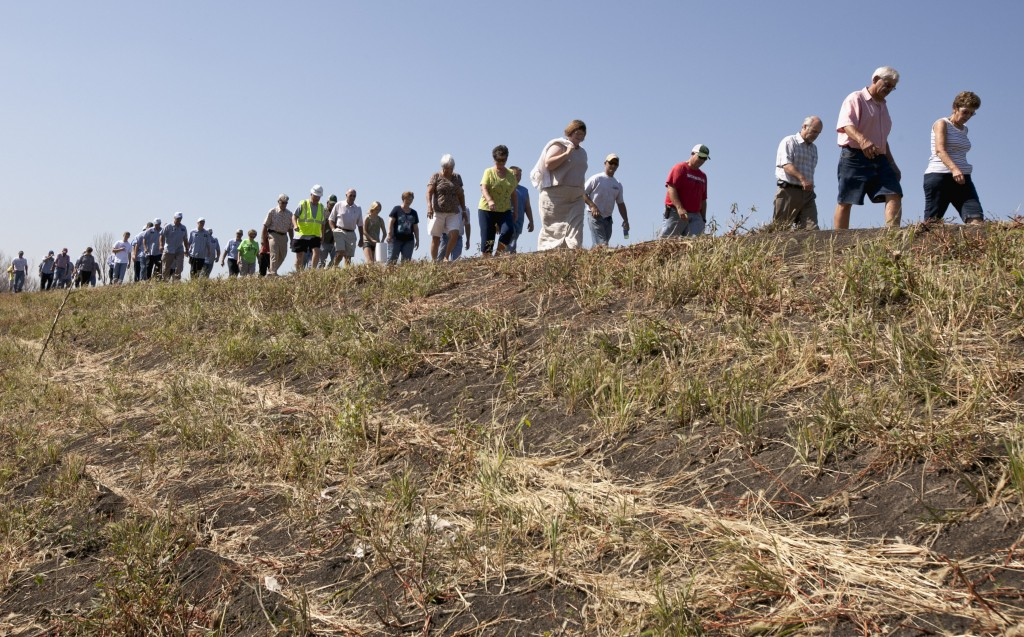 FILE - In this July 26, 2012, file photo, residents of Hamburg, Iowa, in a show of support, walk on the levee the town built the previous year to prot...