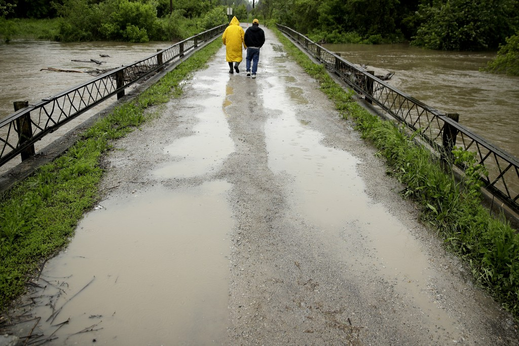 In this photo taken May 21, 2019, Robert Collins, left, and Bobby Joe Branston watch rising waters in the Fishing River from a condemned bridge in the...