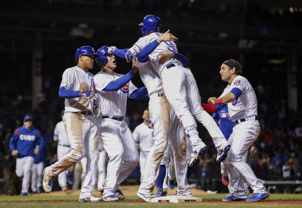 Chicago Cubs' Javier Baez (9) celebrates with teammates after hitting a game winning RBI-single against the Philadelphia Phillies during the ninth inn...