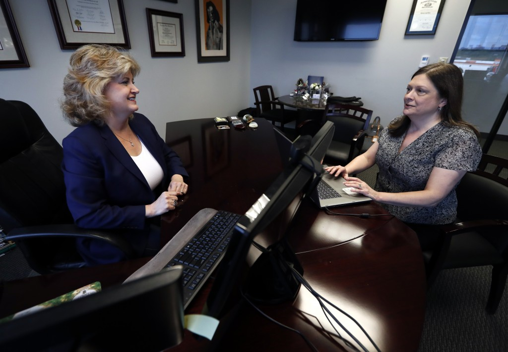 In this Tuesday, May 14, 2019, photo, business owner Meloney Perry, left, of Perry Law, talks with a member of her staff, attorney Karla Roush, at Per