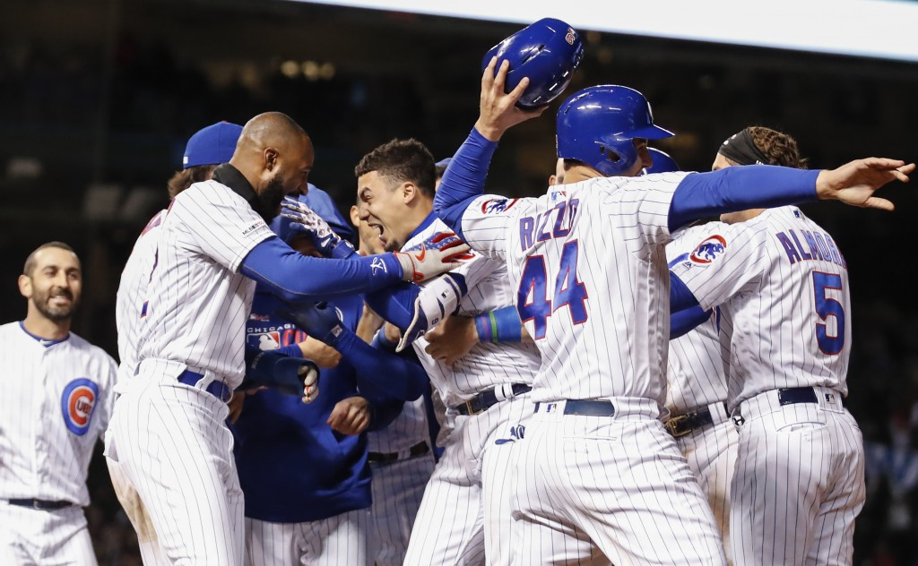 Chicago Cubs' Javier Baez, center, celebrates with teammates after hitting a game winning RBI-single against the Philadelphia Phillies during the nint...