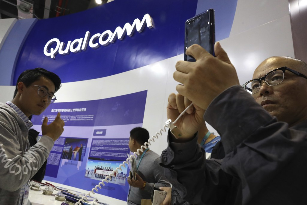 FILE - In this Nov. 6, 2018 file photo, attendees look at the latest technology from Qualcomm at the China International Import Expo in Shanghai. Qual...