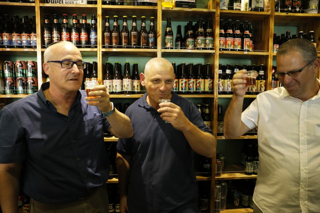 Prof. Aren Maeir, from Bar Ilan University, left, raises a toast with Dr Yitzchak Paz, from the Israeli Antiquities Authority, center, and Prof. Yuval...