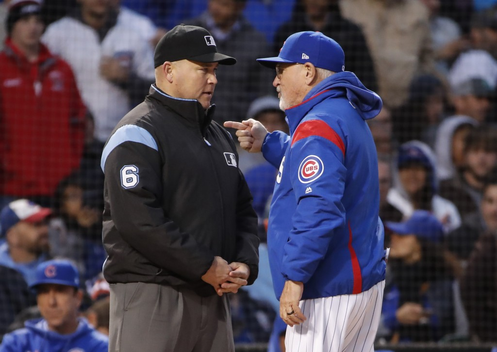 Chicago Cubs manager Joe Maddon, right, argues a call against his team with umpire Mark Carlson, left, during the fourth inning of a baseball game, Tu...