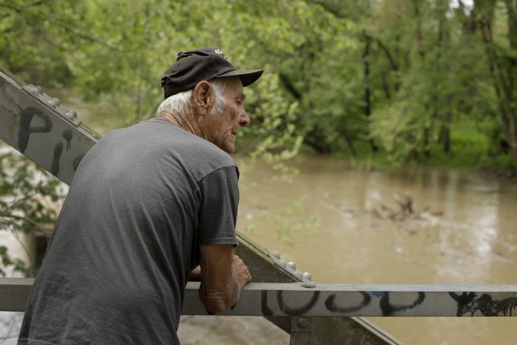 In this photo taken May 8, 2019, Elmer Sullivan checks out high water in the Fishing River in the small community of Mosby, Mo. Sullivan and nearly ha...