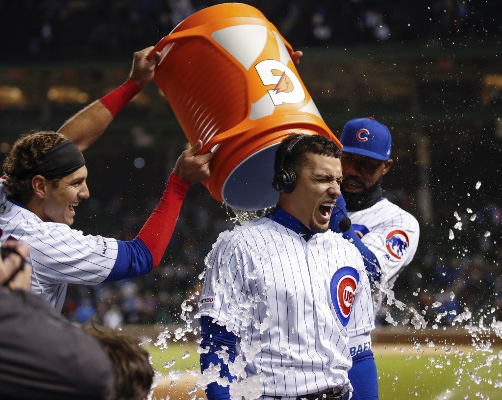 Chicago Cubs' Albert Almora Jr., left, and Jason Heyward, right, douse Javier Baez, center, with ice cubes after Baez hit a game winning RBI-single ag