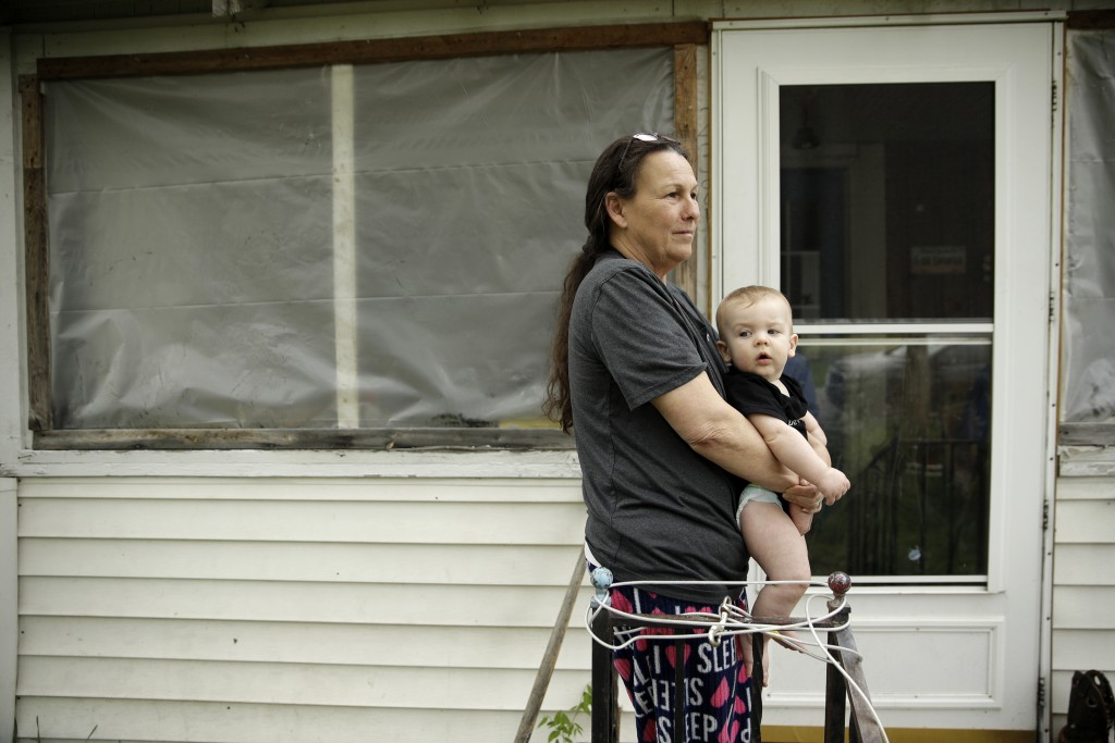 In this photo taken April 24, 2019, Tammy Kilgore with her grandson Tucker Kazzell, 8 months, talks about the times her house has flooded in the small...