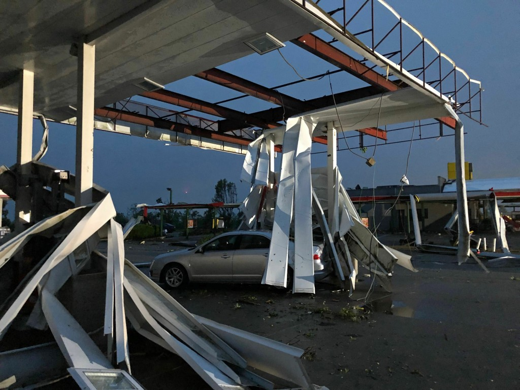 A car is trapped under the fallen metal roof of the Break Time gas station and convenience store in tornado-hit Jefferson City, MO., Thursday, May 23,...