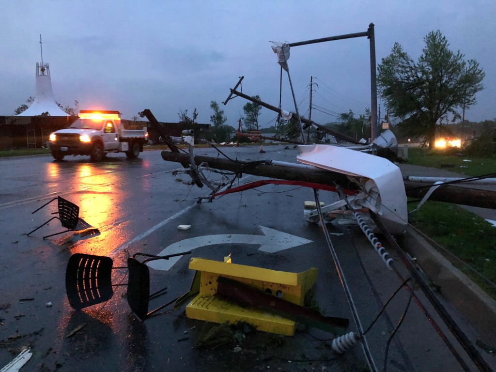 Plastic chairs lie in the road and metal from a damaged gas station roof is twisted around a downed power line in Jefferson City Missouri Thursday, Ma...