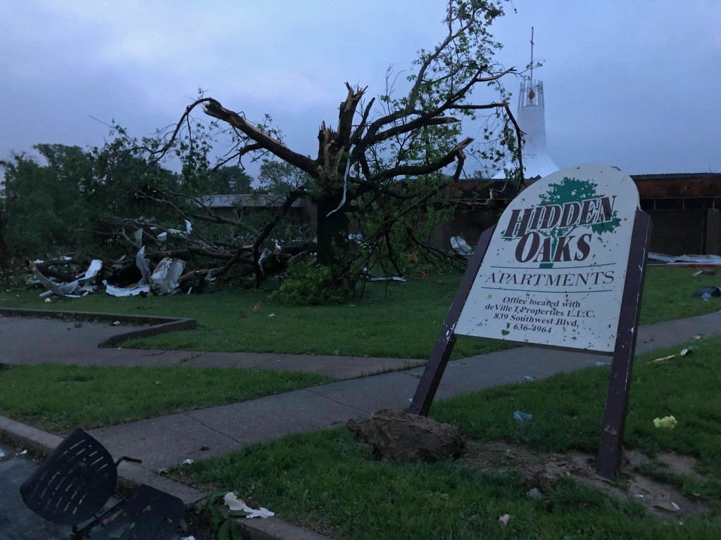 The sign for the Hidden Oaks apartment complex in Jefferson City Missouri stands bent Thursday, May 23, 2019, from a tornado in front of a tree that w...