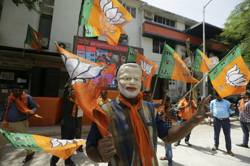 A supporters of India's ruling Bharatiya Janata Party wears mask of Indian Prime Minister Narendra Modi as he celebrates early trends of party's victo...
