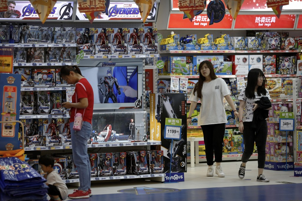 Customers shop near a section selling Marvel Avengers toys by American toymaker Hasbro at a toy store in Beijing, Thursday, May 23, 2019. An escalatin...