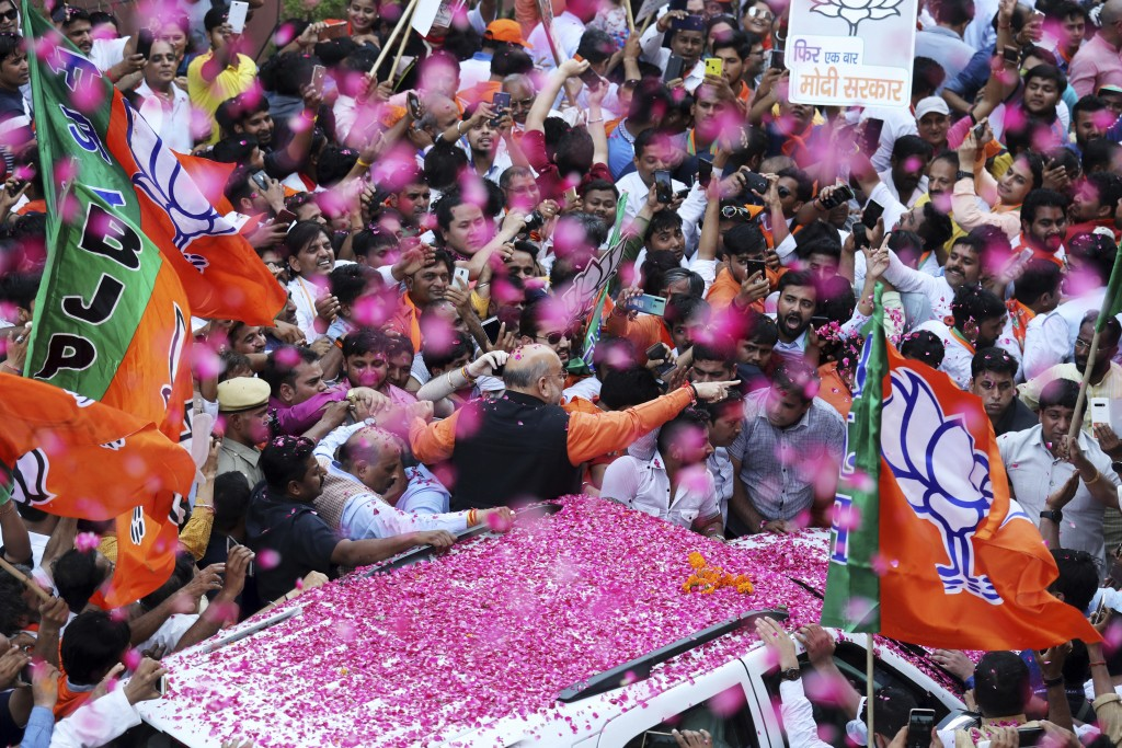 India's ruling Bharatiya Janata Party (BJP) President Amit Shah is showered with flower petals as he arrives at the party office in new Delhi, India, ...