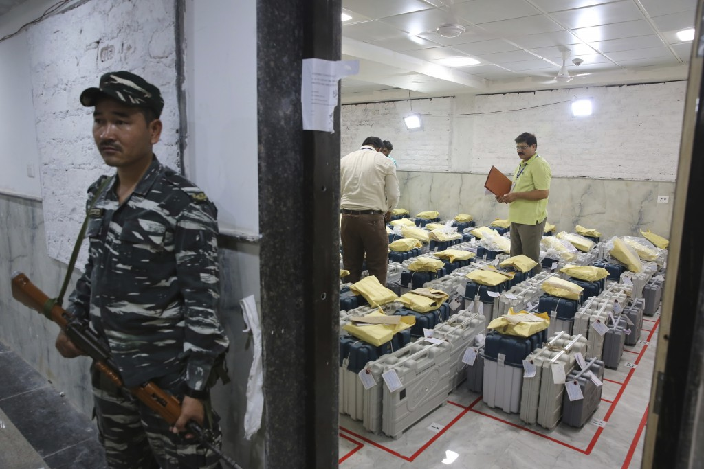 An Indian paramilitary soldier stands guard outside a room where voting machines are stored as counting of votes in India's massive general elections ...