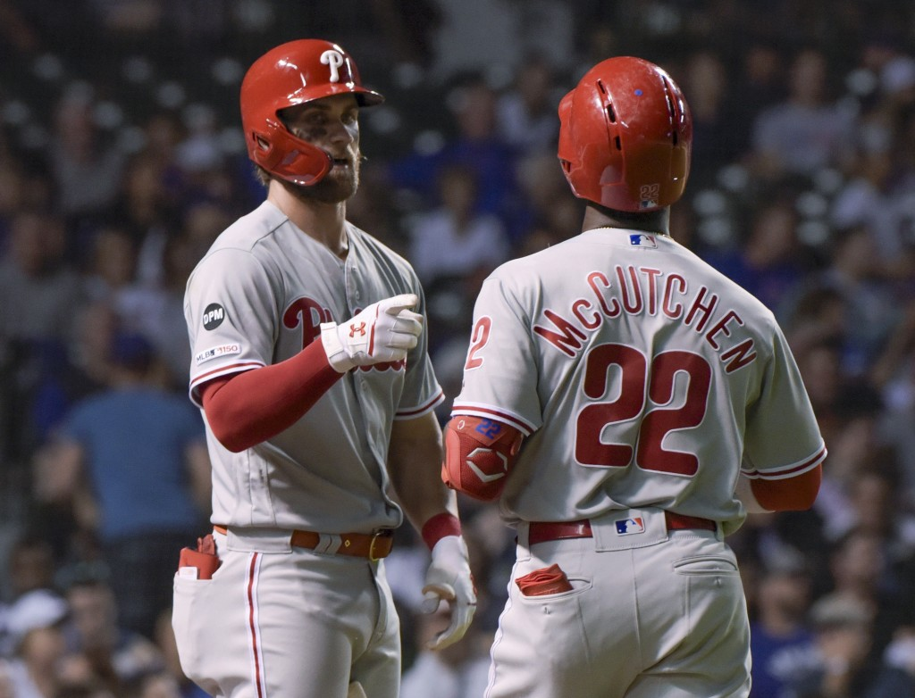 Philadelphia Phillies' Bryce Harper (3) congratulates Andrew McCutchen on his eighth-inning home run against the Chicago Cubs during a baseball game W