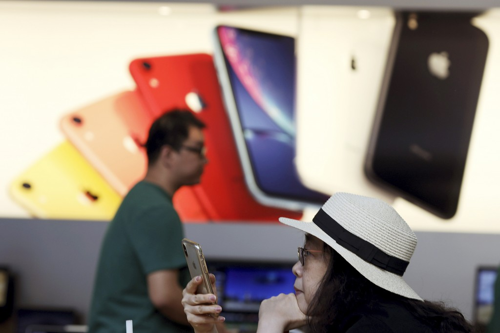 FILE - In this Friday, May 10, 2019, file photo, a customer looks at her iPhone at an Apple store in Beijing. Few U.S. companies are more vulnerable t...