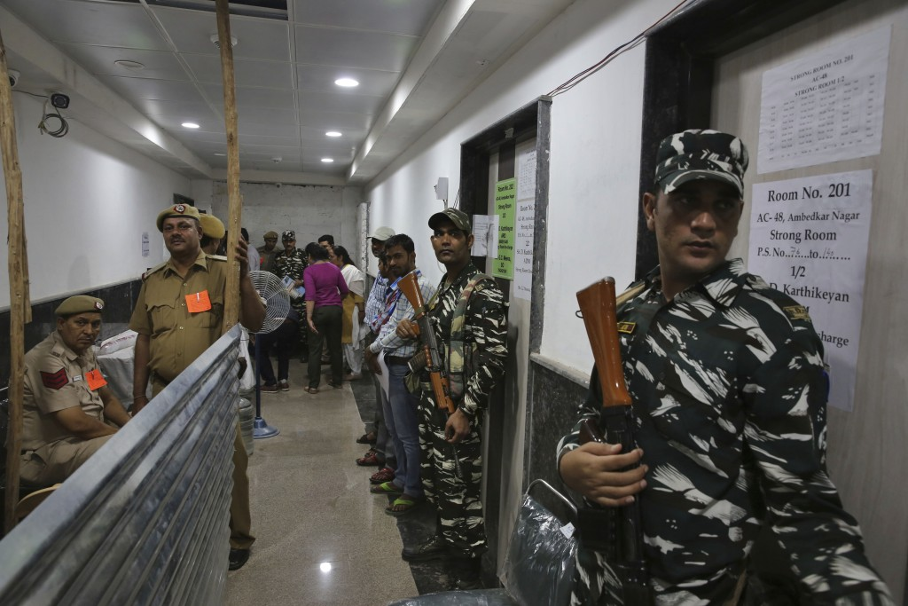 Indian paramilitary force soldiers stand guard outside a room where voting machines are stored as counting votes of India's massive general elections ...