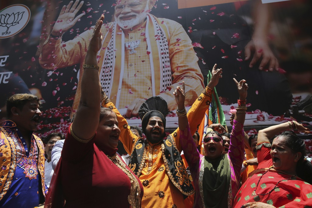 Bharatiya Janata Party (BJP) workers celebrate outside BJP headquarters in Mumbai, India, Thursday, May 23, 2019. Indian Prime Minister Narendra Modi ...