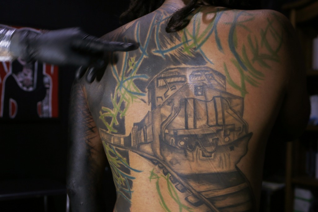 """In this Sept. 6, 2018 photo, tattoo artist known as Enrique inks the image of the train known as """"La Bestia"""" on the arm of a migrant from El Salvador,..."""