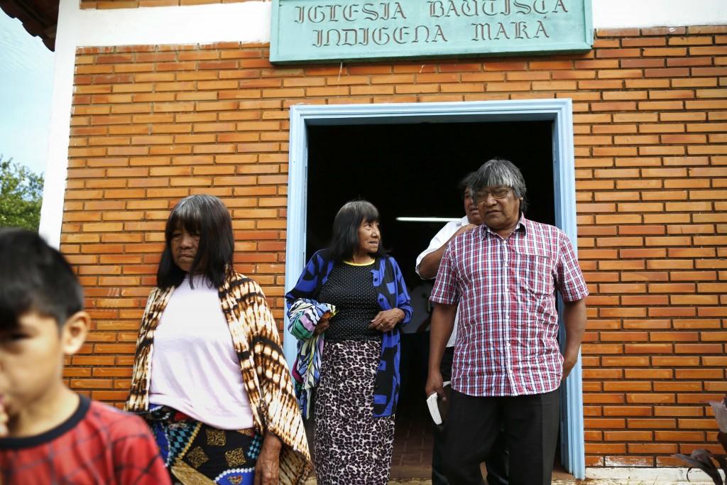 Maka indigenous leader-in-training Tsiweyenki, or Gloria Elizeche in Spanish, center, talks to interim chief Mateo Martinez as they leave a worship se...