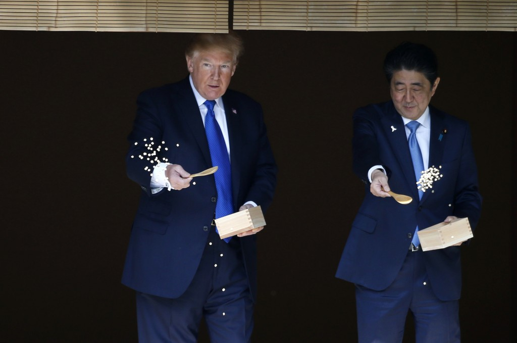 FILE - In this Nov. 6, 2017, file photo, U.S. President Donald Trump, left, and Japanese Prime Minister Shinzo Abe feed carp before their working lunc...
