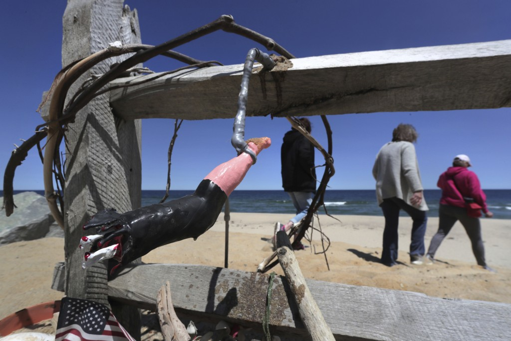 In this May 22, 2019, photo, three women pass a makeshift memorial at Newcomb Hollow Beach, where a boogie boarder was bitten by a shark and later die