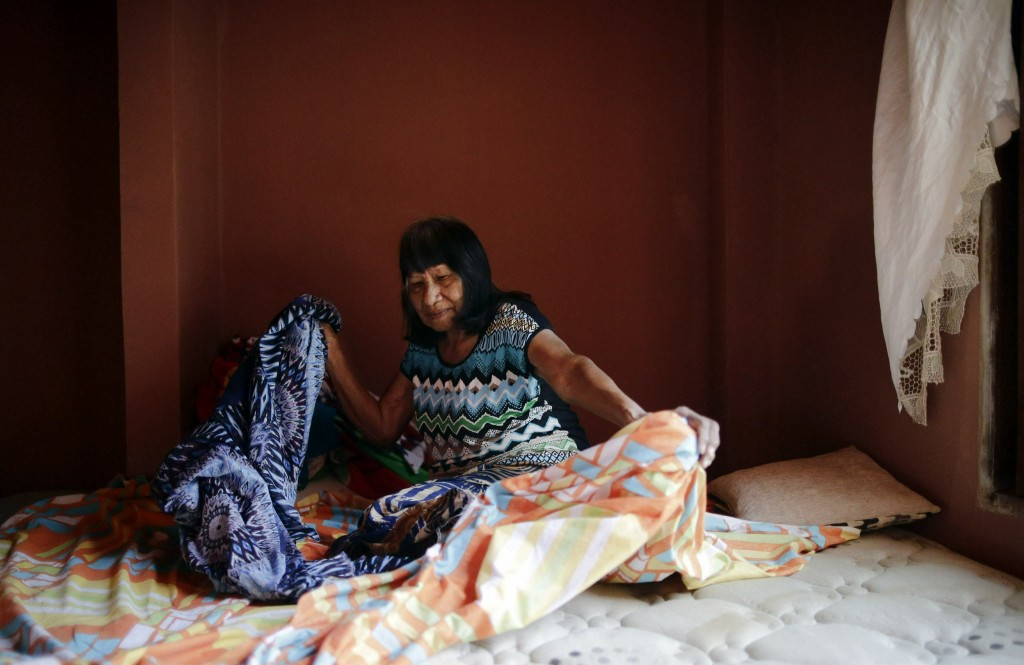 Maka indigenous leader-in-training Tsiweyenki, or Gloria Elizeche in Spanish, makes a bed at her home in Mariano Roque Alonso, Paraguay, Wednesday, Ap