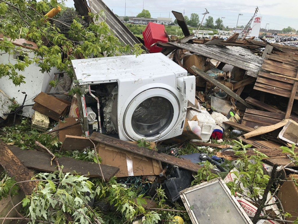 Debris from a home that David Surprenant rents with his family is scattered across the lawn Thursday, May 23, 2019, the morning after a tornado hit Je...