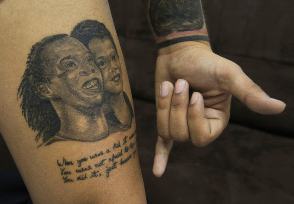 In this April 22, 2019 photo, tattoo artist Ricardo Medina shows his tattoos of Brazilian soccer star Ronaldinho, at a tattoo parlor in Mexico City. L...