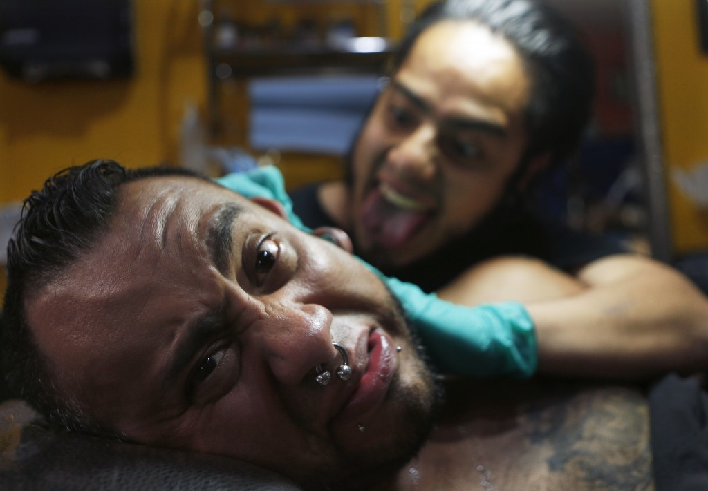 In this April 18, 2019 photo, tattoo artist Lalo Calva inks a tattoo on client Adrian Alonso Rodriguez, a journalist, announcer and dubbing artist, at...