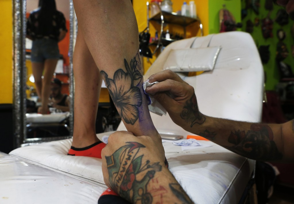 In this April 18, 2019 photo, tattoo artist Lalo Aguayo cleans a tattoo of a hibiscus flower on the leg of Laura Reyes, a dance student, at the Corona...