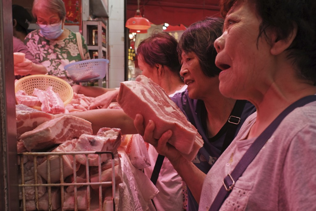 In this Thursday, May 16, 2019, file photo, customers buy frozen pork at a local market in Hong Kong. A case of African swine fever has been detected ...